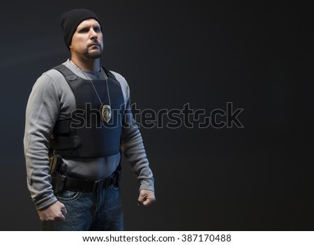 Copy Space of Undercover Law Enforcement Special Agent with weapon. He looks angry and is making a fist, ready to fight. - stock photo