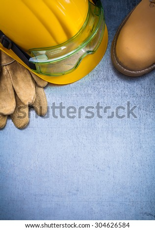Copy space of waterproof boots protective leather gloves building helmet and safety glasses on scratched metallic background construction concept. - stock photo