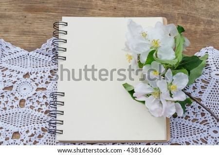 Copy space on empty pages of a notebook for memos, personal diary, on background of wood and crocheted napkin with flowers on the side.  - stock photo