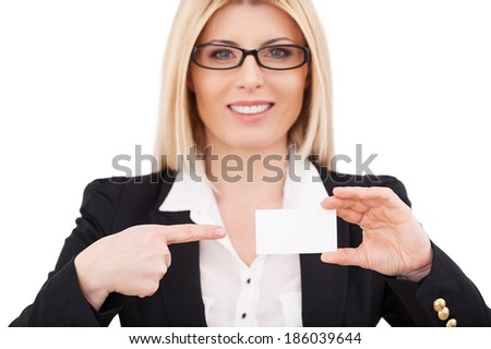 Copy space on her business card. Beautiful mature businesswoman pointing her business card and smiling while standing isolated on white - stock photo