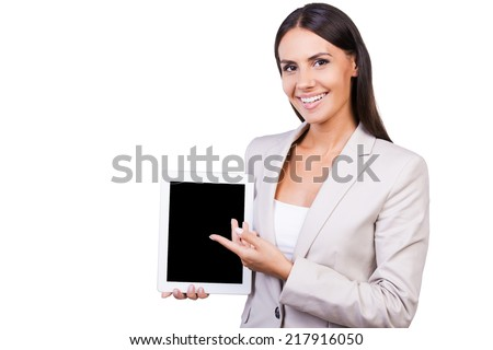 Copy space on her tablet. Beautiful young businesswoman in suit holing digital tablet pointing it while standing isolated on white background - stock photo