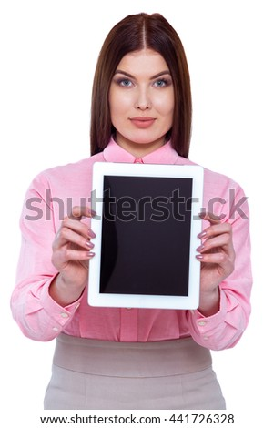 Copy space on her tablet. Cheerful young woman holding digital tablet and pointing at it while standing against white background - stock photo