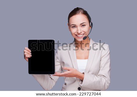 Copy space on her tablet. Confident young female operator holding digital tablet while standing against grey background  - stock photo