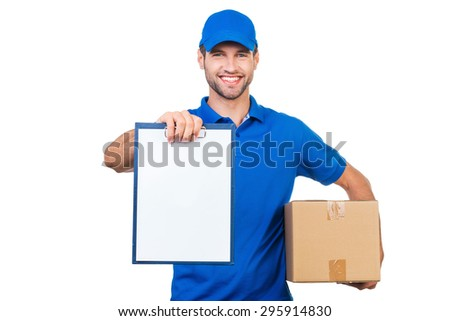 Copy space on his clipboard. Cheerful young courier stretching out clipboard and smiling while standing against white background - stock photo