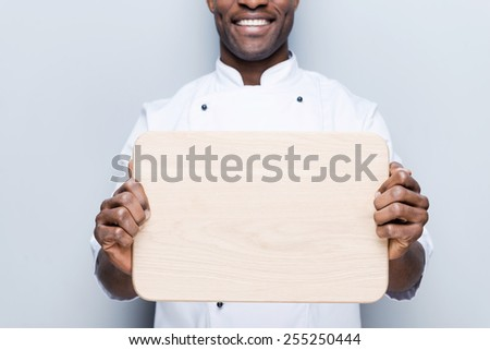Copy space on his cutting board. Close-up of confident young African chef in white uniform holding wooden cutting board and smiling while standing against grey background - stock photo