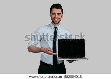 Copy space on his laptop.  Good looking young man in white shirt and tie pointing copy space on his laptop and smiling while standing against grey background