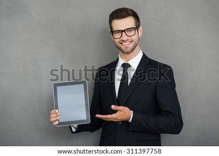 Copy space on his tablet. Cheerful young businessman holding digital tablet and pointing at it while standing against grey background - stock photo