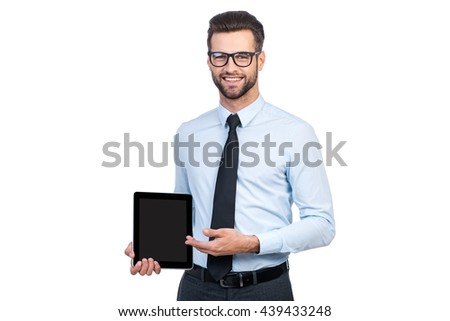 Copy space on his tablet. Confident young handsome man in shirt and tie holding digital tablet and pointing it with smile while standing against white background  - stock photo