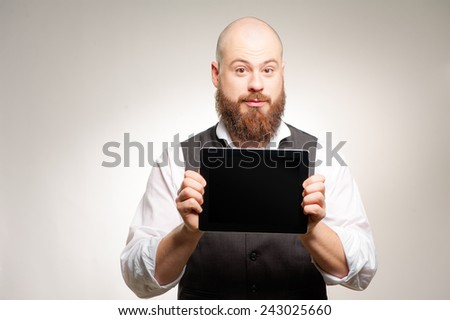 Copy space on his tablet. Handsome young bearded caucasian man holding digital tablet with smile while standing on grey background - stock photo