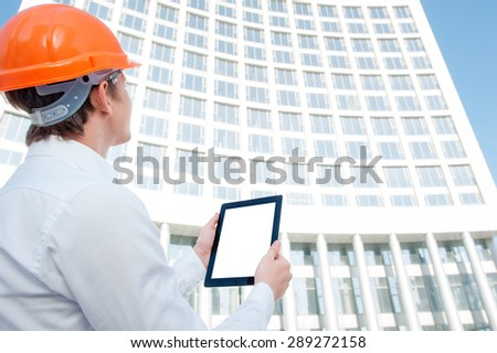Copy space on screen. Young man in hardhat using tablet computer while standing outdoors and against building structure. - stock photo