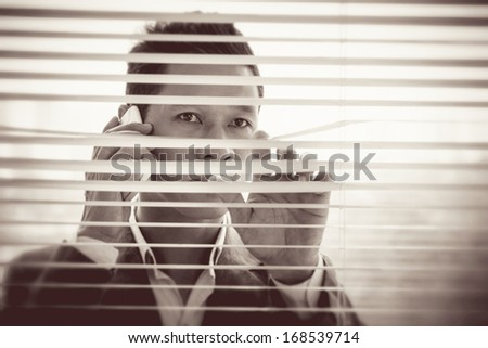 Copy-spaced image of a businessman having serious telephone call through the shutter on the foreground