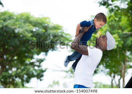 Copy-spaced image of a cheerful father having fun with his little son in the park - stock photo