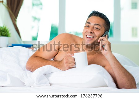 Copy-spaced image of a cheerful man talking by phone lying in the bed  - stock photo