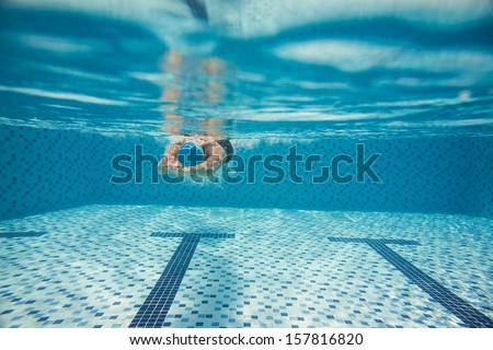 Copy-spaced image of a diving man in a swim suit under water on the foreground - stock photo