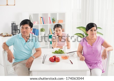 Copy-spaced image of a family in conflict sitting in the kitchen before lunch  - stock photo