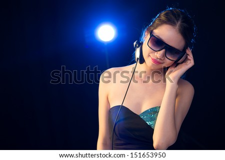 Copy-spaced image of a female DJ listening to the music in headphones isolated on black - stock photo