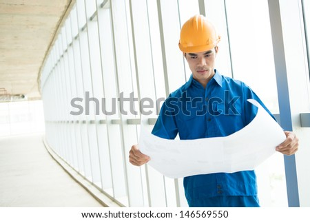 Copy-spaced image of a foreman concentrated on the blueprint - stock photo