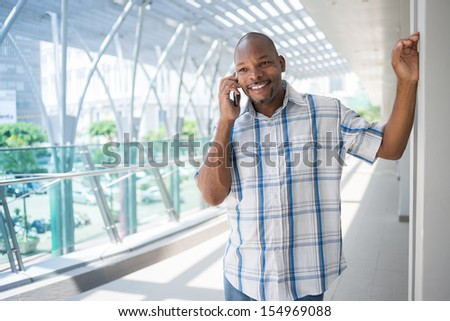 Copy-spaced image of a handsome black man talking by phone inside - stock photo