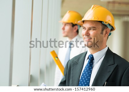 Copy-spaced image of a happy constructor worker in a hardhat on the foreground - stock photo