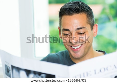Copy-spaced image of a man reading the newspaper and smiling