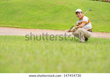 Copy-spaced image of a mature golf player preparing for the training on the lawn - stock photo