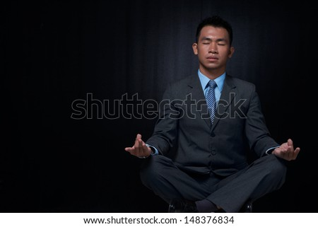 Copy-spaced image of a relaxed businessman resting in yoga position against a black background - stock photo
