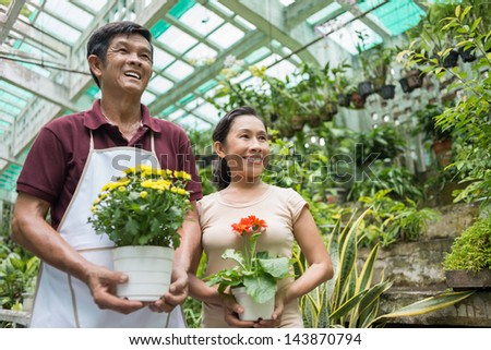 Copy-spaced image of a senior couple standing and holding flowerpots in the greenhouse - stock photo