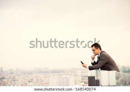 Copy-spaced image of a serious businessman standing on the roof and holding a mobile phone  - stock photo