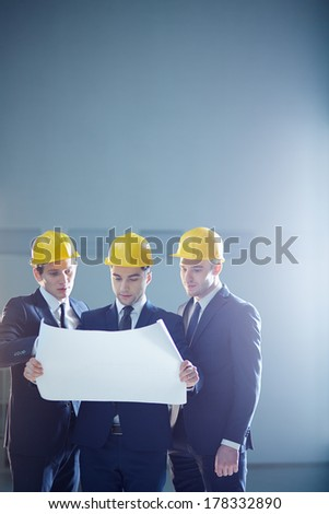 Copy-spaced image of a three construction workers holding a draft and discussing something  - stock photo