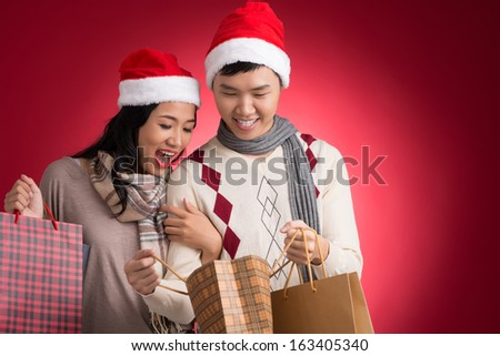 Copy-spaced image of a young amazing couple with paperbags full of presents over a red background - stock photo