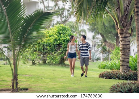 Copy-spaced image of a young cheerful couple walking in the park together  - stock photo
