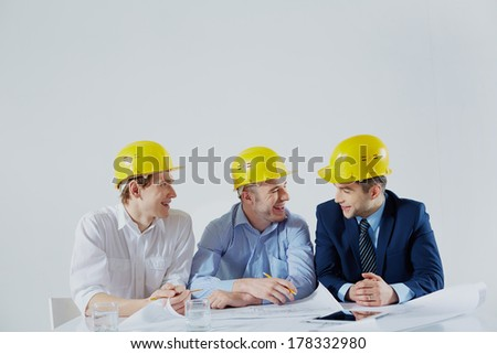 Copy-spaced image of cheerful engineers sharing the ideas over white  - stock photo