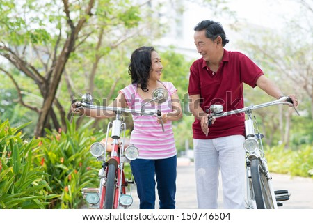 Copy-spaced image of happy seniors carrying their bicycles in the park - stock photo