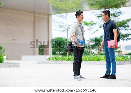 Copy-spaced image of young students talking during the break on the foreground - stock photo