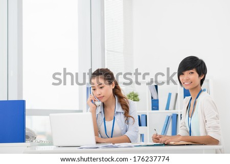 Copy-spaced portrait of a businesswoman making notes while her colleague talking by phone at the workplace  - stock photo