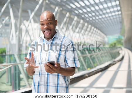Copy-spaced portrait of a cheerful black businessman with a gadget in hands  - stock photo
