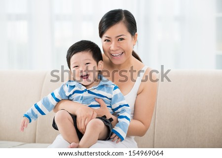 Copy-spaced portrait of a cheerful mother and her laughing son looking at camera - stock photo