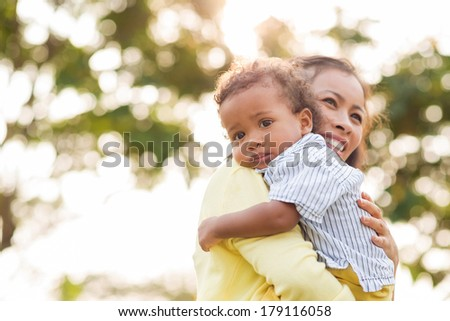 Copy-spaced portrait of a little boy looking at camera while his mother bonding him on the foreground  - stock photo