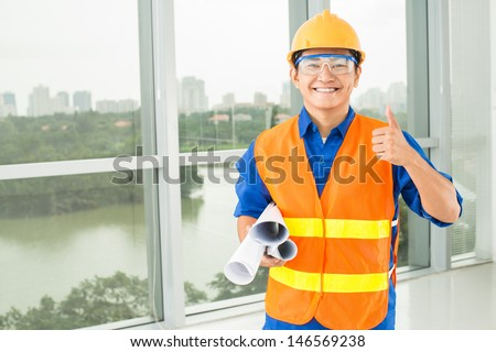Copy-spaced portrait of a smiling engineer thumbing up and looking at camera - stock photo