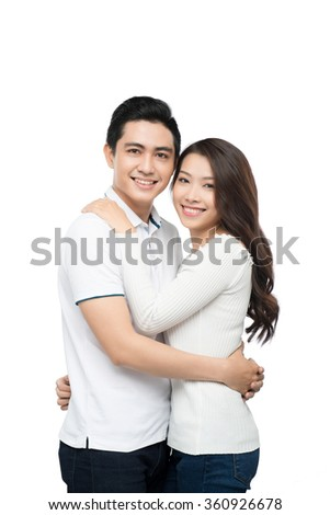 Copy-spaced portrait of a young couple in-love smiling and looking at camera - stock photo