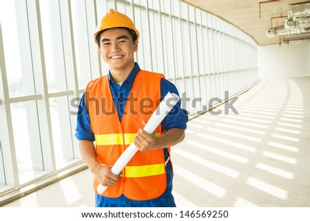 Copy-spaced portrait of a young engineer smiling and looking at camera - stock photo