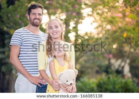 Copy-spaced portrait of a young friendly family standing and posing at camera in the park