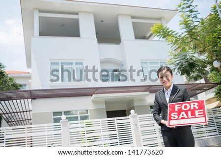 """Copy-spaced portrait of an attractive female realtor standing near the house """"??for sale"""" - stock photo"""