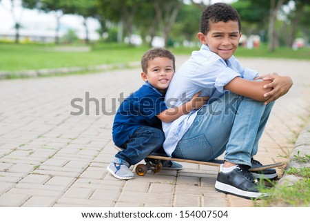 Copy-spaced portrait of brothers sitting on the skateboard in the park - stock photo