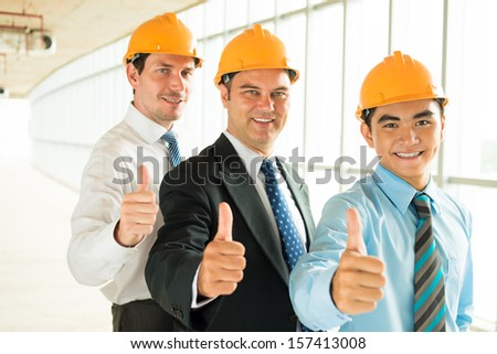 Copy-spaced portrait of cheerful engineers showing 'ok'?� sign on the foreground - stock photo