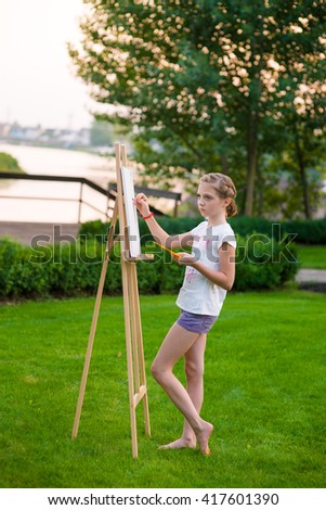 Copying the sight for paper on easel. Little lovely girl is concentrated on her painting. Serious face while being busy with her hobby. Full body shot. - stock photo