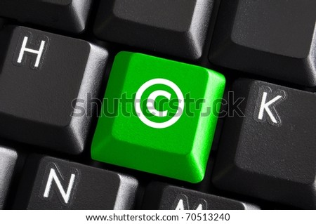 copyright concept with green button on computer keyboard - stock photo