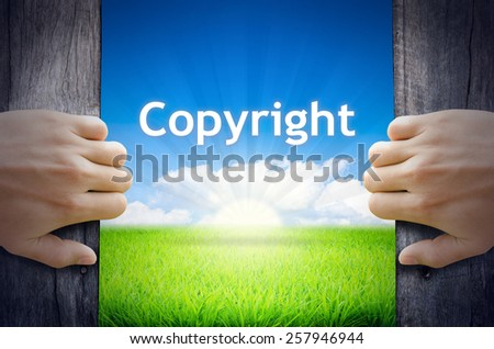 Copyright. Hand opening an old wooden door and found Copyright word floating over green field and bright blue Sky Sunrise. - stock photo