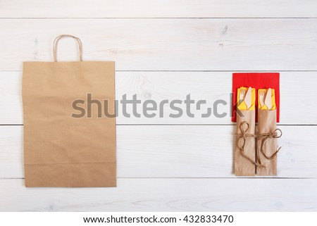 Copyspace at white wooden background for menu or recipe. Food delivery, take away with brown paper bag. Food background. Fork and knife wrapped in paper, cutlery at wood, top view with copy space - stock photo