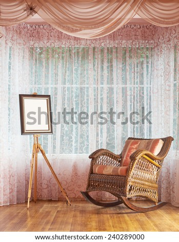 Copyspace empty picture frame on the wooden easel and next to wicker rocking chair, composition against the window's curtains background - stock photo